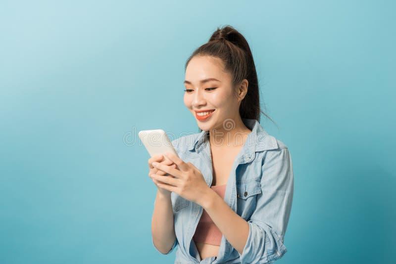 Telefone celular asiático da terra arrendada da mulher 20s e sorriso sobre o fundo azul fotografia de stock