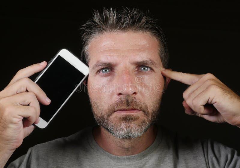 Telefone celular atrativo e considerável novo da terra arrendada do homem do viciado do Internet contra sua cara no app social do imagem de stock royalty free