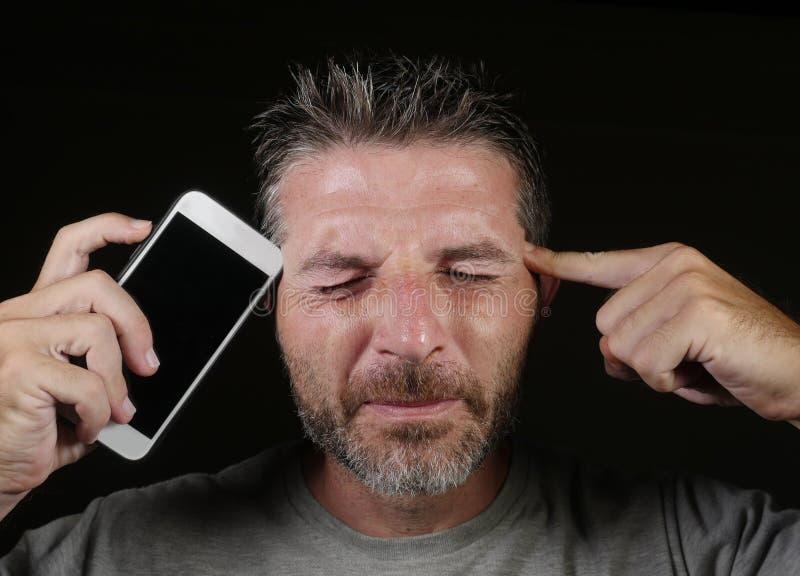 Telefone celular atrativo e considerável novo da terra arrendada do homem do viciado do Internet contra sua cara no app social do fotos de stock