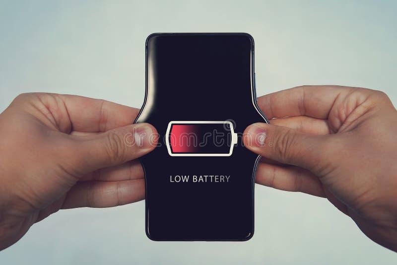 telefone celular com a baixa bateria na tela Todos os gráficos da tela são compostos aumente a bateria, carga fraca stretc das mã imagens de stock