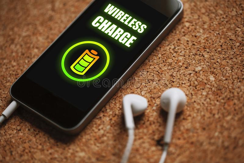 Telefone celular com função sem fio do carregador na tela e nos fones de ouvido brancos foto de stock royalty free