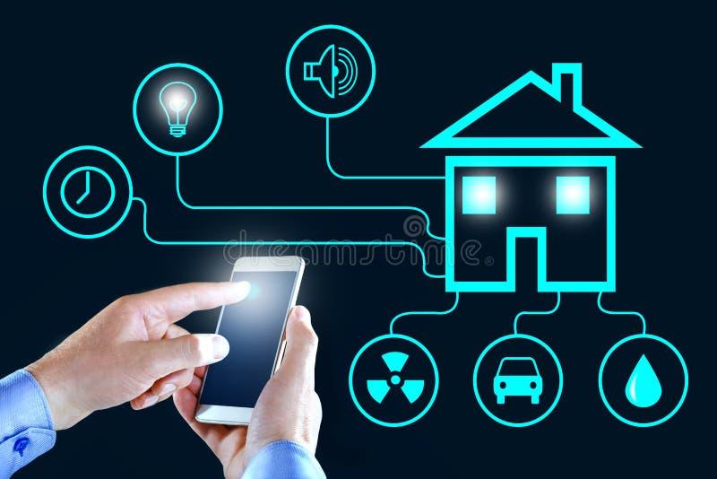Telefone celular com o app esperto da casa Mãos do homem com smartphone usando o hom esperto fotografia de stock royalty free
