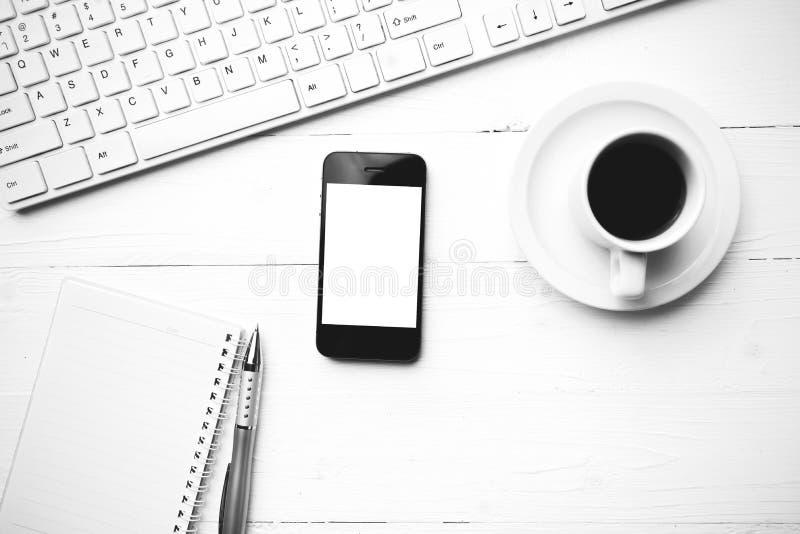 Telefone celular com o chiqueiro preto e branco da cor do copo do computador e de café fotografia de stock royalty free
