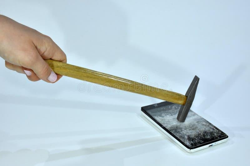 Telefone celular com a tela quebrada por um martelo imagem de stock