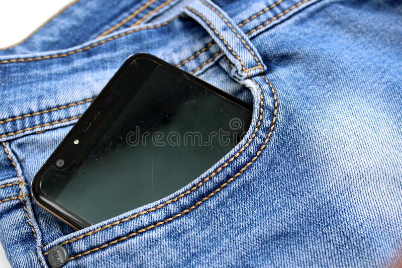 Telefone celular com uma tela preta no bolso de calças da sarja de Nimes