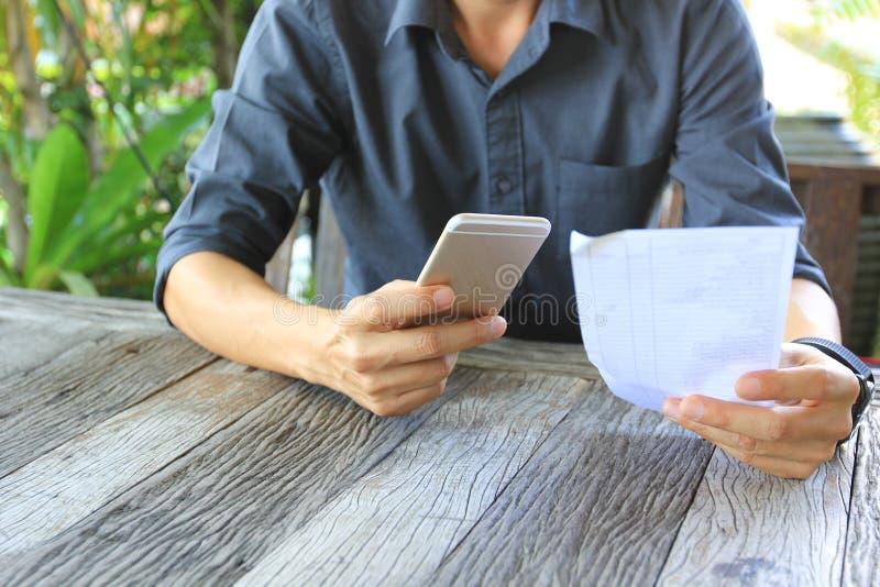 Telefone celular da terra arrendada do homem de neg?cios com papel da conta no restaurante imagens de stock
