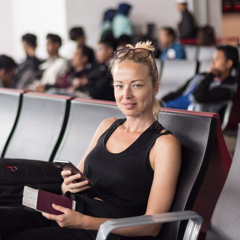 Telefone celular da terra arrendada do viajante, passaporte e passagem de embarque fêmeas louros bronzeados ocasionais ao esperar imagens de stock