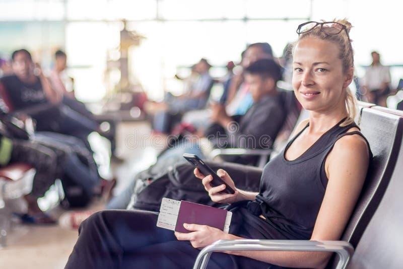 Telefone celular da terra arrendada do viajante, passaporte e passagem de embarque fêmeas louros bronzeados ocasionais ao esperar fotografia de stock royalty free