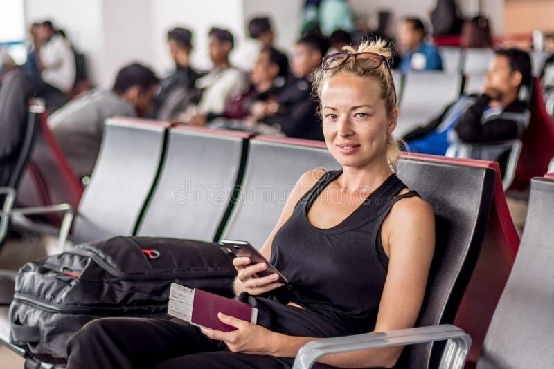Telefone celular da terra arrendada do viajante, passaporte e passagem de embarque f?meas louros bronzeados ocasionais ao esperar foto de stock royalty free