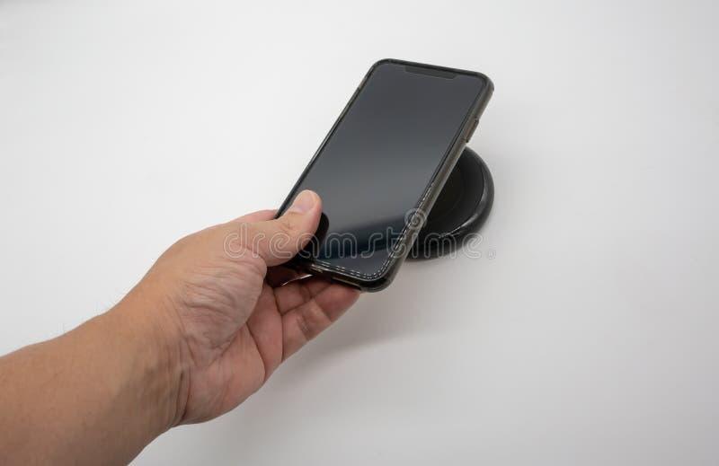 Telefone celular da terra arrendada da mão sobre o carregador sem fio preto o fotografia de stock royalty free