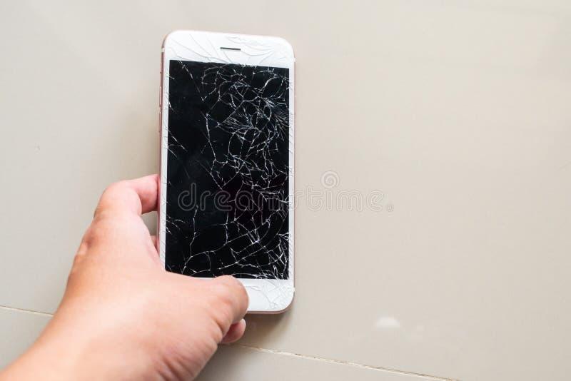 Telefone celular da terra arrendada da m?o com a tela de vidro quebrada imagem de stock