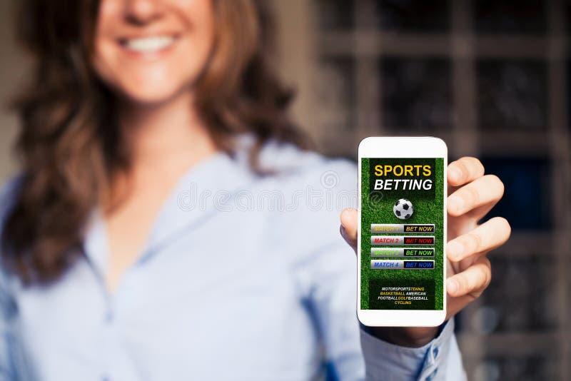 Telefone celular da terra arrendada da mulher com os esportes que apostam o app fotografia de stock