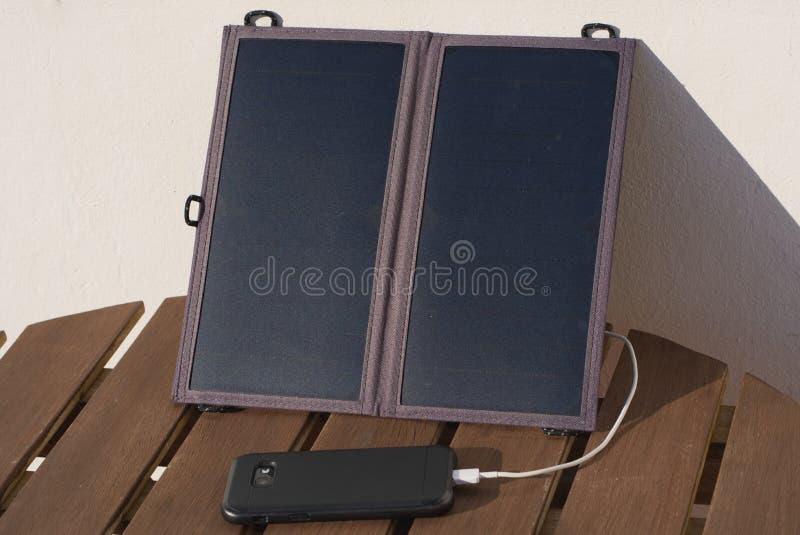 Telefone celular de carregamento do carregador solar imagens de stock