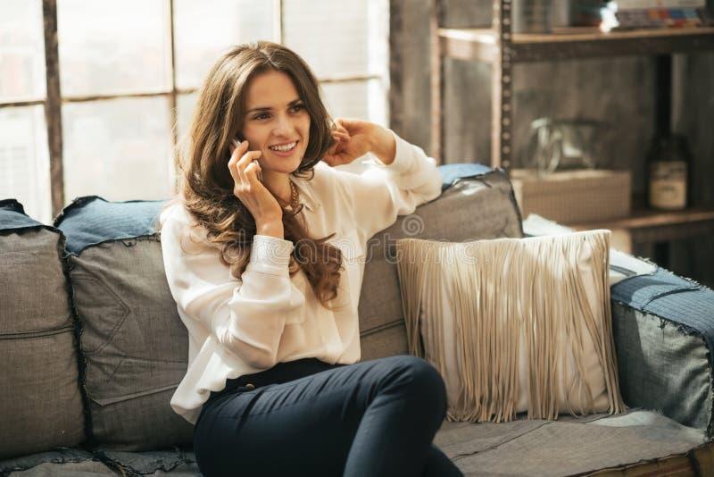 Telefone celular de fala da mulher no apartamento do sótão imagem de stock