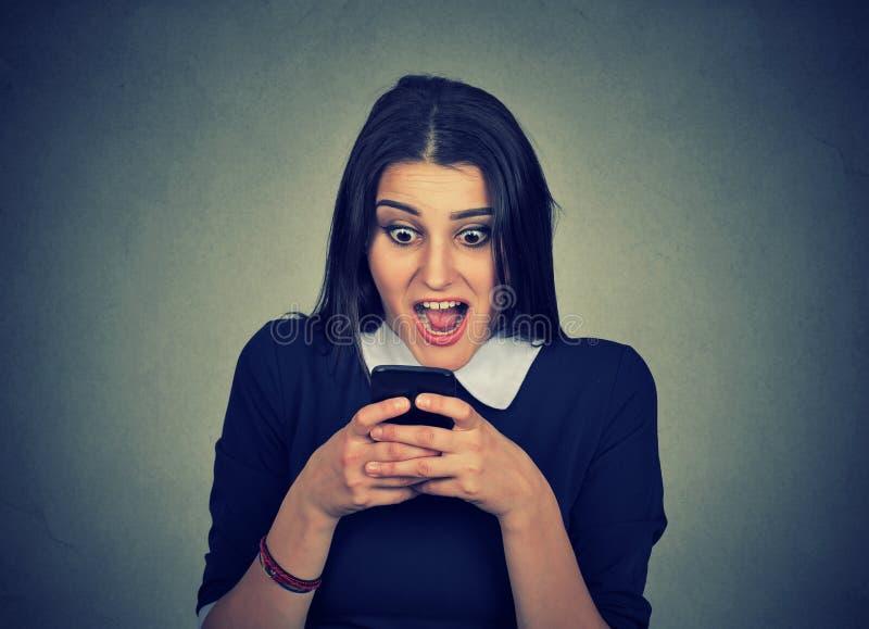 Telefone celular de observação chocado da jovem mulher foto de stock