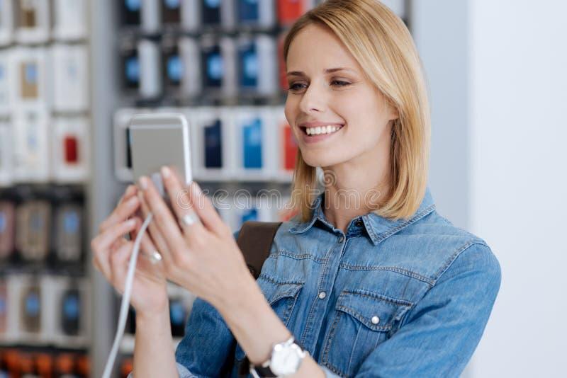 Telefone celular de sorriso bonito do molde dos testes da senhora na exposição foto de stock