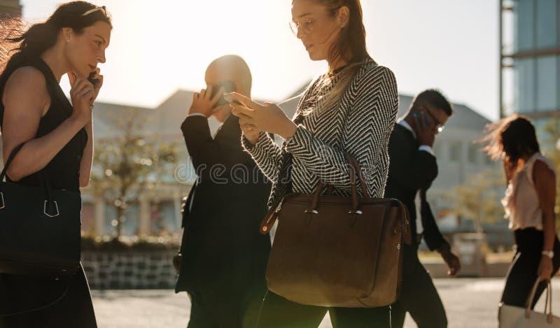 Telefone celular de utilização ocupado dos povos ao andar na rua ao escritório fotografia de stock