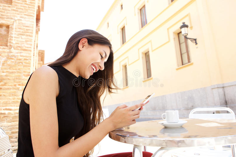 Telefone celular de vista fêmea de sorriso imagem de stock royalty free