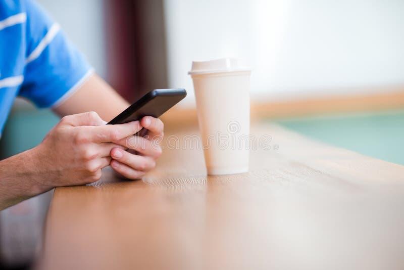 Telefone celular do close up e vidro do café no café Homem que usa o smartphone móvel Menino que toca em uma tela de seu smarthon imagem de stock