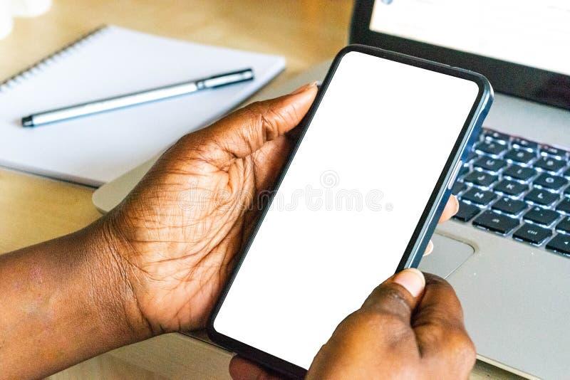 Telefone celular do tela táctil, na mão da mulher africana Telefone esperto da terra arrendada fêmea preta no fundo exterior verd fotos de stock