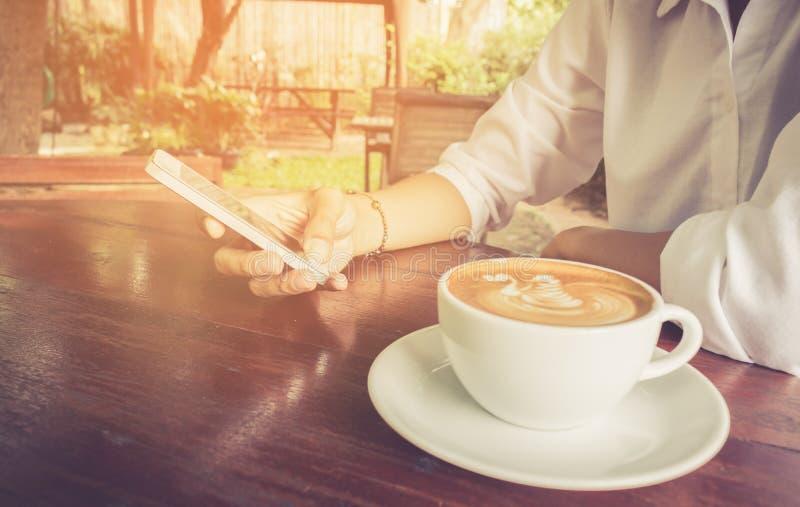 Telefone celular do uso da mulher com tom do vintage do copo de café imagem de stock royalty free