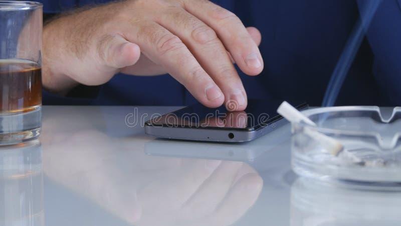 Telefone celular do uso de BusinessmMan que fuma um charuto e que bebe Alcoholan no escritório usando um livro de bolso para redi fotografia de stock royalty free