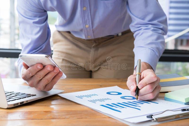 Telefone celular do uso do homem de negócios o homem analisa o gráfico & o inve financeiros imagem de stock royalty free