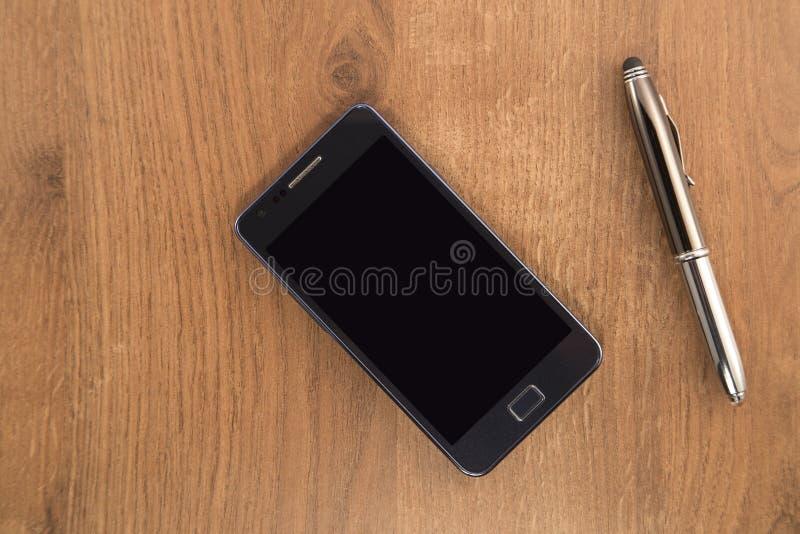 Telefone celular e a pena fotografia de stock