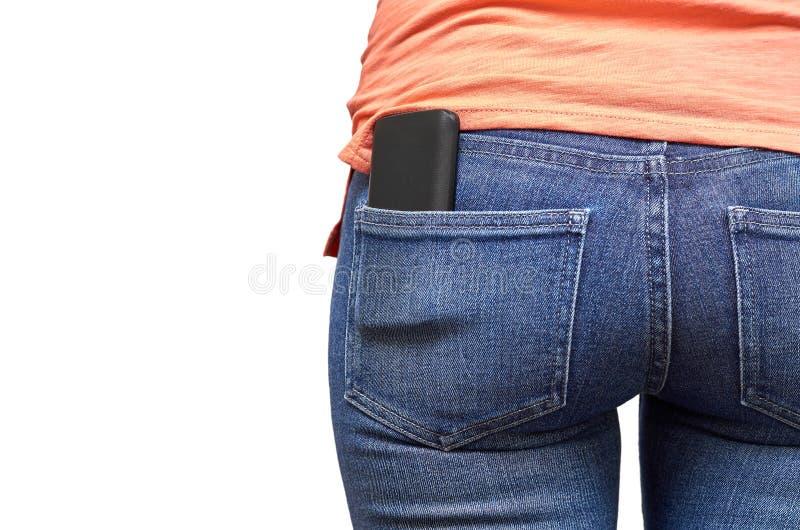 Telefone celular em um bolso da calças de ganga Isolado no fundo branco imagem de stock