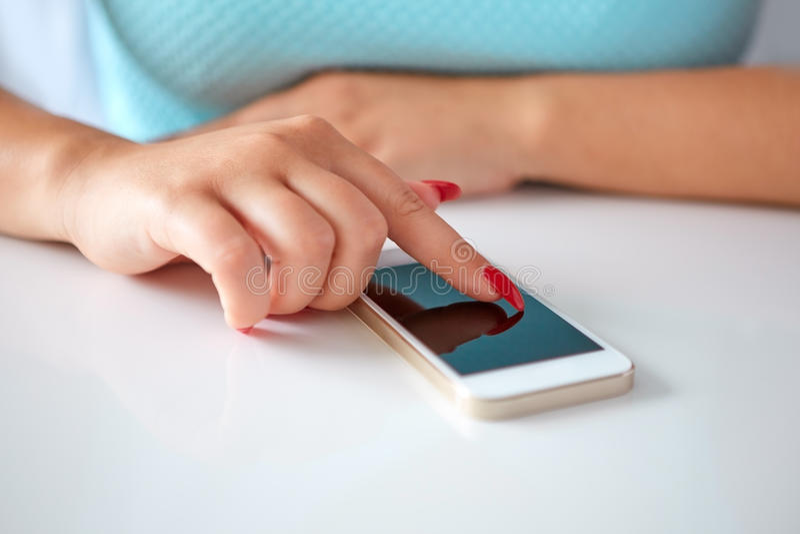 Telefone celular em uma tabela e em uma jovem mulher brancas foto de stock
