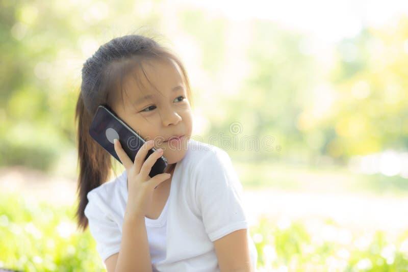 Telefone celular esperto feliz e falando da criança asiática do retrato bonito no parque natural no verão, telefone celular da cr fotos de stock royalty free