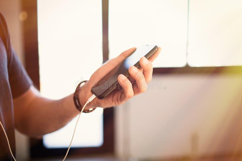 Telefone celular masculino da terra arrendada das mãos, verificando redes sociais no smartphone em casa fotografia de stock