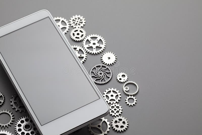 Telefone celular moderno branco com a tela cinzenta vazia e as engrenagens pequenas na tabela imagens de stock royalty free