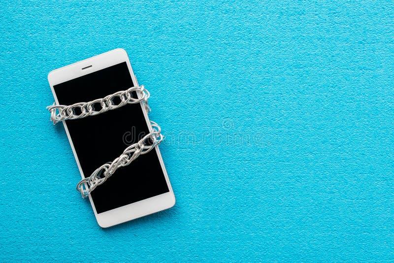 Telefone celular moderno com o isolado fechado chain no fundo azul fotos de stock royalty free