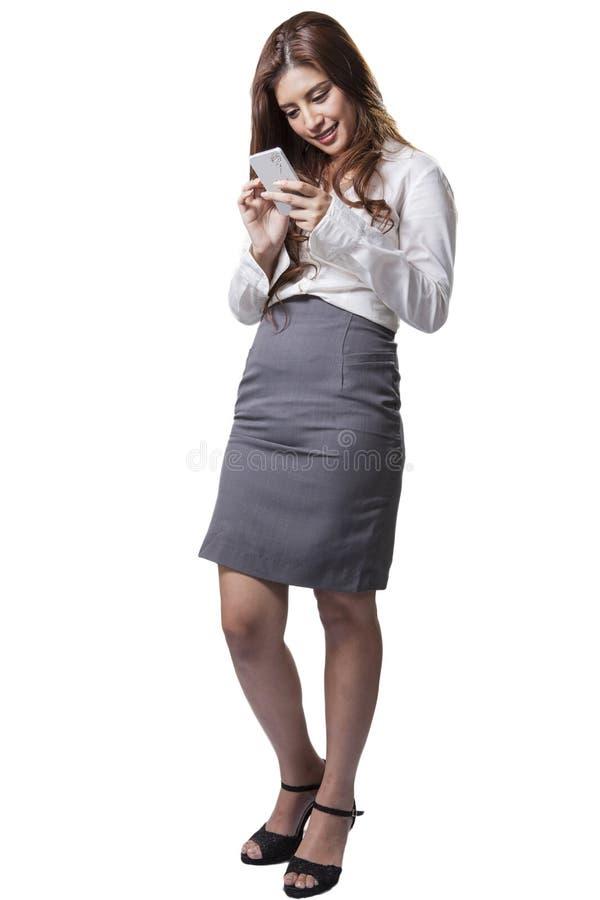 Telefone celular moreno do texto da mulher de negócios imagem de stock royalty free