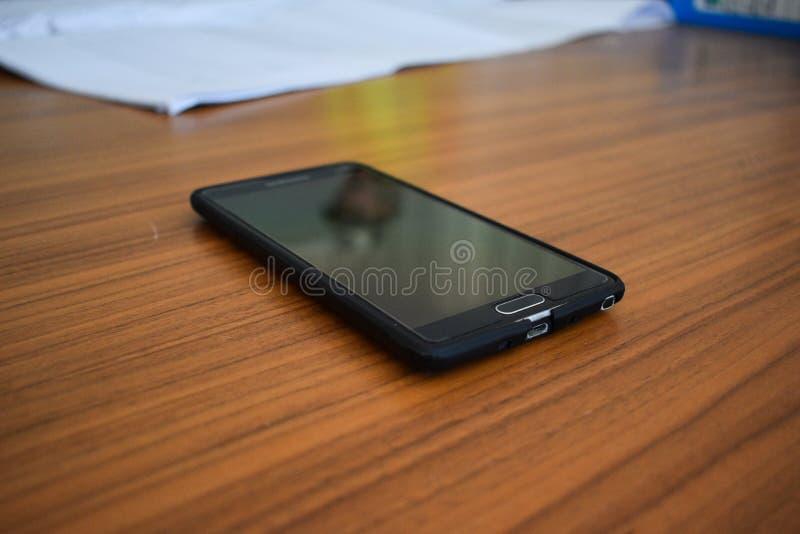 Telefone celular na tabela de reunião fotografia de stock