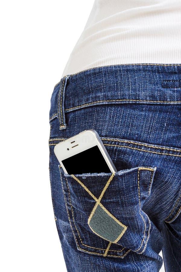 Telefone celular no bolso traseiro da calças de ganga fotografia de stock royalty free