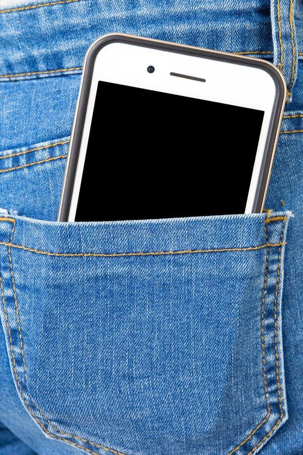 Telefone celular no bolso traseiro das calças de brim da menina imagens de stock royalty free