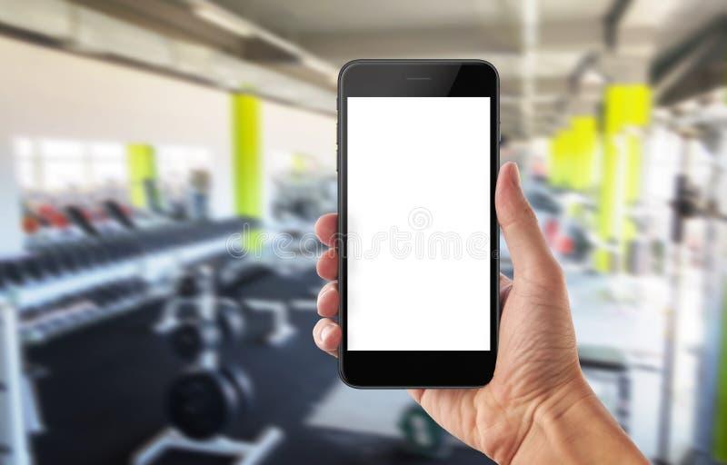 Telefone celular no gym do esporte Tela branca isolada para o modelo imagens de stock