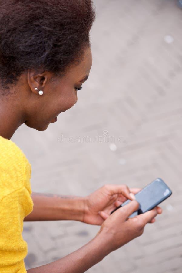 Telefone celular novo da terra arrendada da mulher negra e vista da tela fotografia de stock royalty free