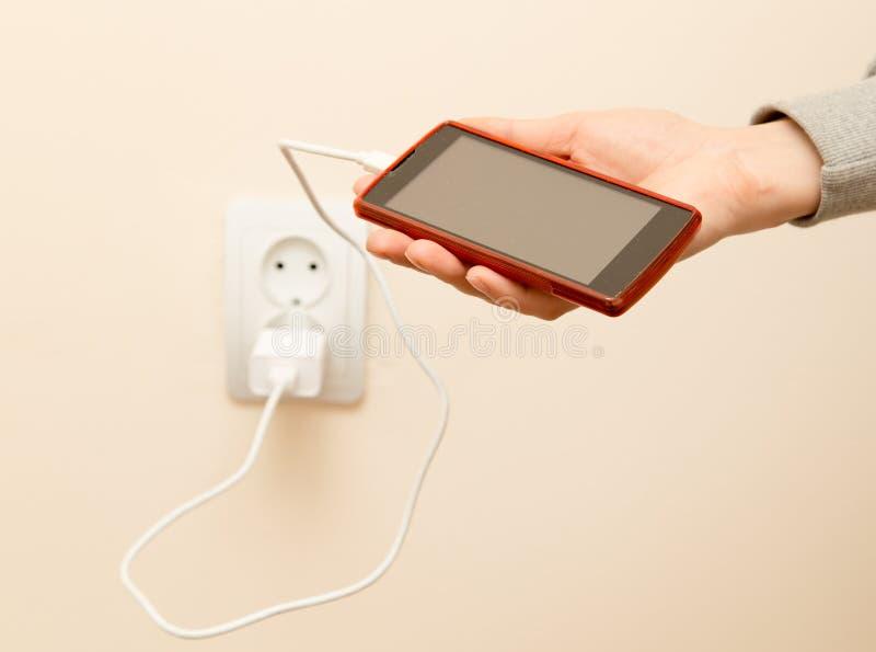 Telefone celular que carrega em sua mão imagem de stock