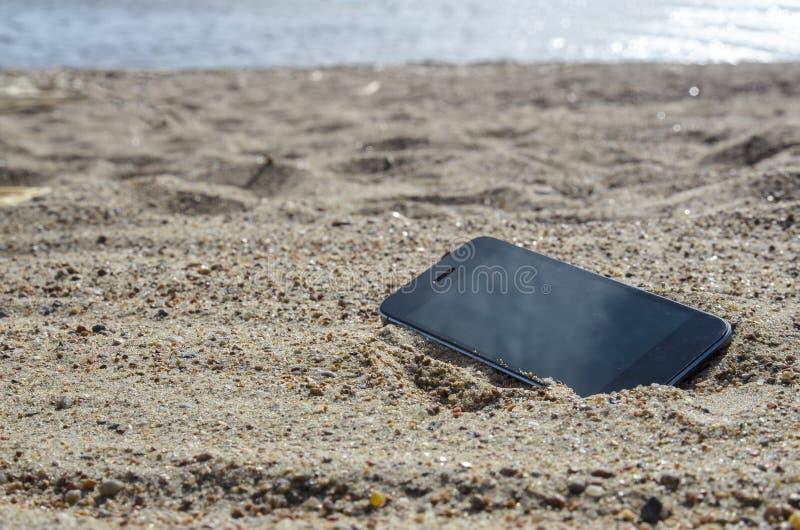 Telefone celular que encontra-se na praia na areia telefones à prova de intempéries, conceito perdido do telefone, perda dos dado fotografia de stock royalty free