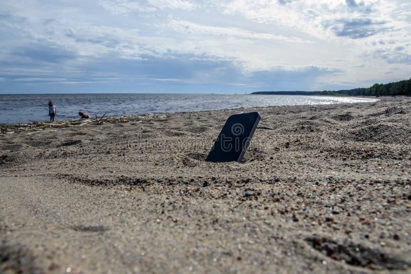 Telefone celular que encontra-se na praia na areia telefones à prova de intempéries, conceito perdido do telefone fotografia de stock