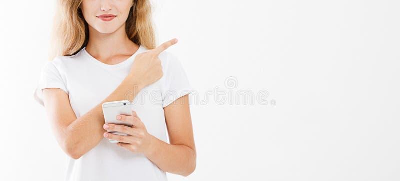Telefone celular 'sexy' da tela vazia da posse da mulher, apontando o dedo isolado no fundo branco, mão que guarda o telefone pre imagens de stock