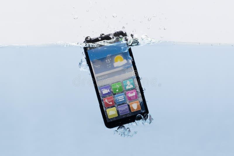 Telefone celular submerso na água foto de stock