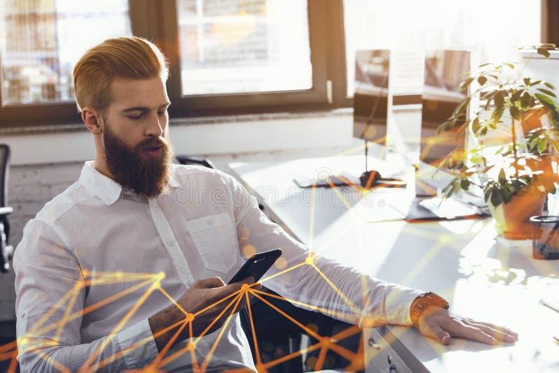 Telefone celular tocante do homem de negócios no escritório durante o trabalho fotos de stock royalty free