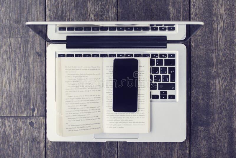 Telefone celular vazio com livro e o portátil abertos fotografia de stock