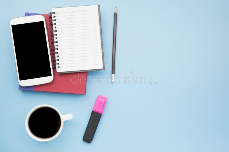 Telefone celular vermelho da tampa do caderno e copo branco do café preto no bl imagens de stock