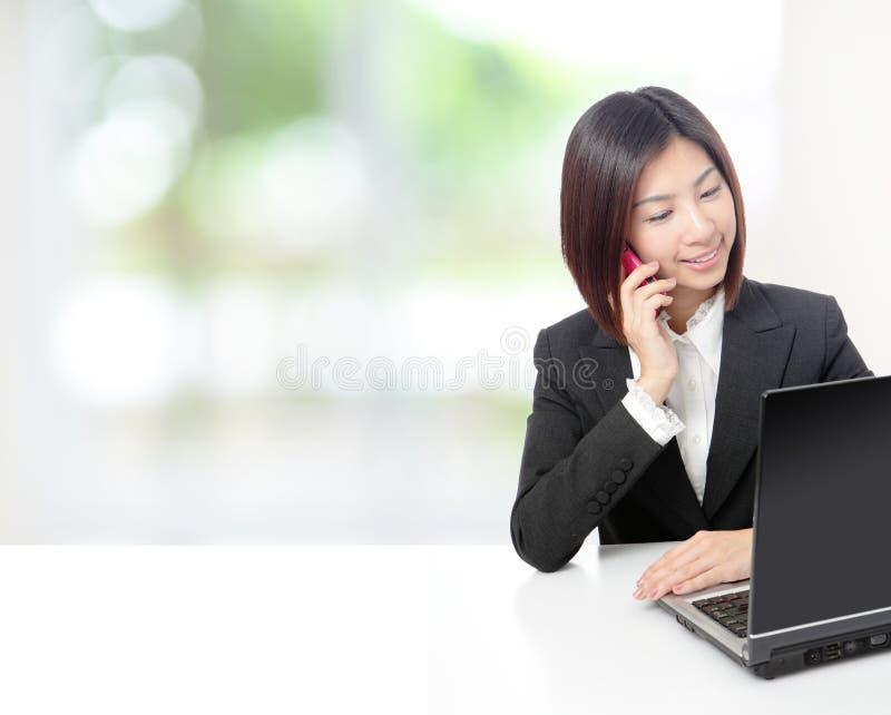 Telefone da mulher de negócio e computador faladores da utilização fotografia de stock royalty free