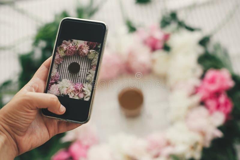 Telefone da terra arrendada da mão e foto da tomada da bebida do café no quadro bonito na tabela, configuração lisa do rosa e o b fotos de stock